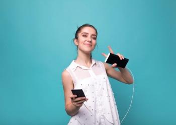Chica con smartphone y Power bank cargando su teléfono inteligente.
