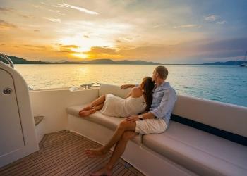 Vacaciones románticas en un yate. Hermosa pareja mirando al atardecer desde el yate.