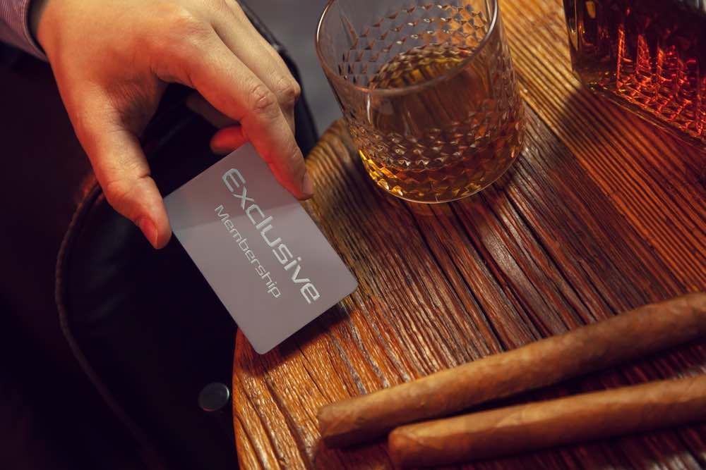 Multimillonario pone su tarjeta VIP de membresía exclusiva sobre la mesa.