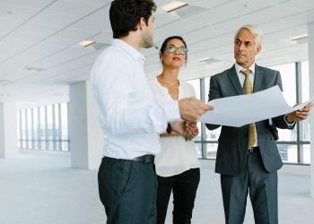 Cerrando negocio. Oficina. Agente inmobiliario mostrando nuevo espacio de oficina a clientes potenciales.