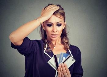 Mujer estresada confundida mirando demasiadas tarjetas de crédito