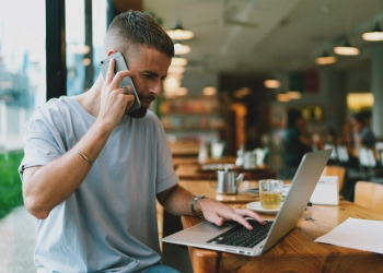 Hombre hablando por teléfono móvil y mirando la pantalla del portátil sentado en una cafetería moderna.