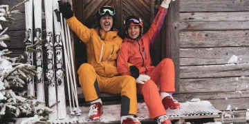 Pareja de esquí deportivo adulto maduro sentado en el refugio de montaña de nieve sonriendo a la cámara.