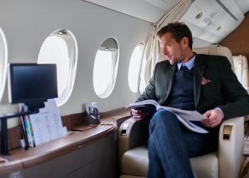 Exitoso hombre de negocios sentado en el interior del avión jet privado.