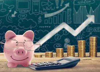 Alcancía, calculadora y monedas sobre una mesa de madera