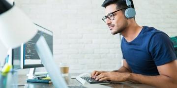 Desarrollador de software programando códigos mientras trabaja desde casa.