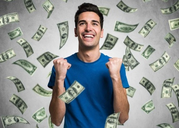 Hombre joven feliz bajo una lluvia de dinero en efectivo.