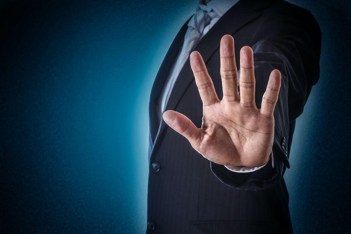 Empresario poniendo la mano hacia adelante en señal de parar