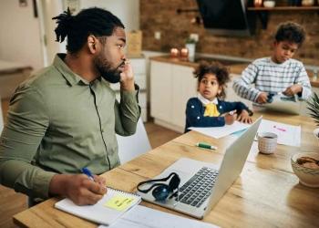 Padre afroamericano que trabaja en casa.