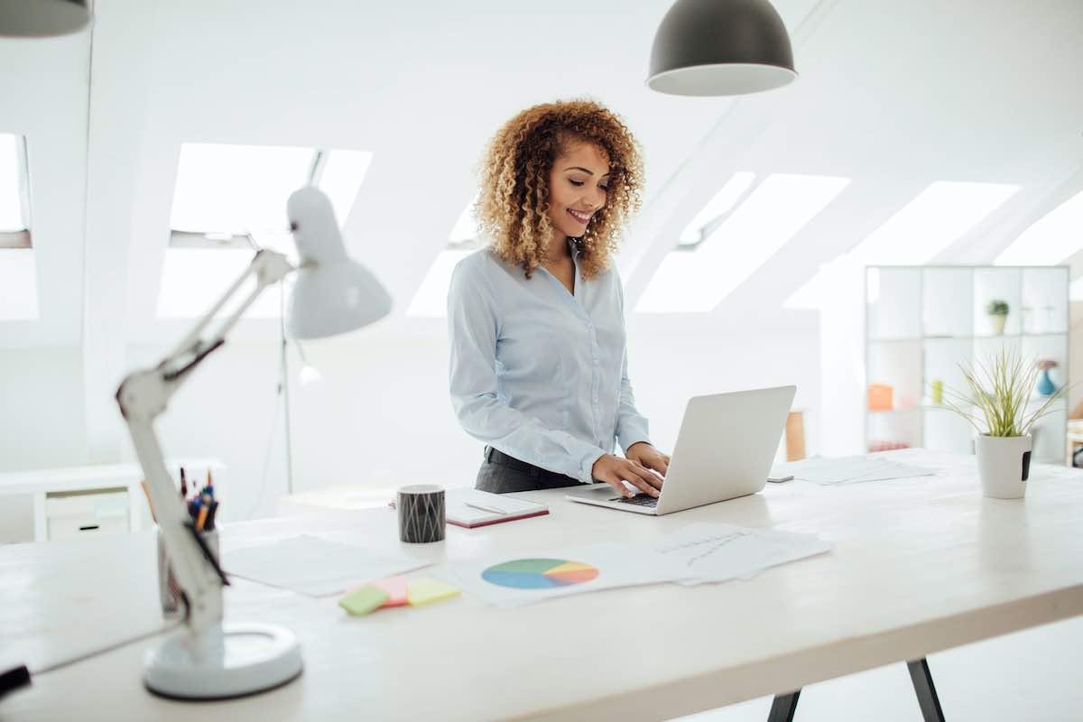Empresaria latina que trabaja en su oficina. Ella está de pie junto al escritorio y usa su computadora portátil.