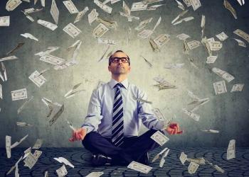 Hombre de negocios meditando bajo la lluvia de dinero