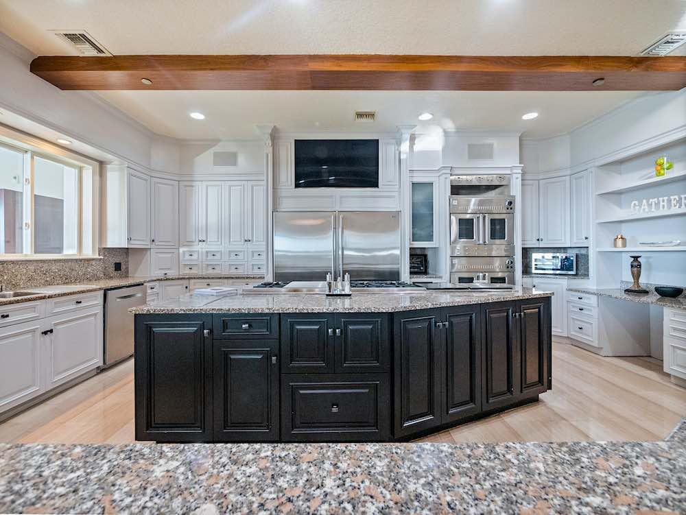 Cocina del chef con gabinetes de madera personalizados e isla para cocina de seis pies con encimera de granito.