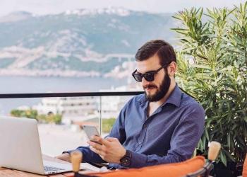 Joven empresario con computadora y teléfono inteligente trabaja desde un restaurante