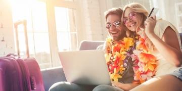 Pareja joven con gafas de sol y accesorios de Hawaii viajar en casa, sentado en el sofá con computadora portátil y la tarjeta de crédito en las manos.