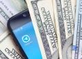Teléfono inteligente con aplicación Telegram y muchos billetes de cien dólares.