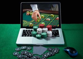Mesa verde con fichas de casino, computadora y tarjetas en el portátil