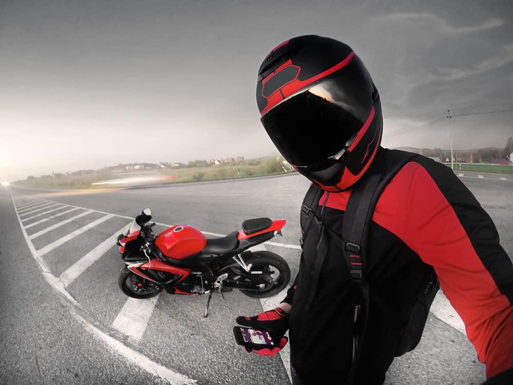 Motorista con casco de alta tecnología se encuentra junto a una motocicleta roja