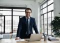 Hombre de negocios en gafas posando en su oficina moderna, en traje formal mira a cámara, muestra confianza en el éxito en el lugar de trabajo.