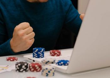 Joven jugando con su computadora en sitios web de apuestas. ruleta de póquer de casino en línea.
