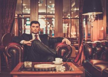 Millonario sentado en un interior de lujo del club VIP