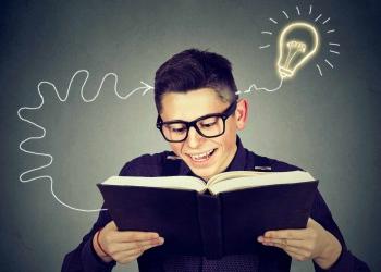 Hombre joven con gafas leyendo libro se le ocurre una idea