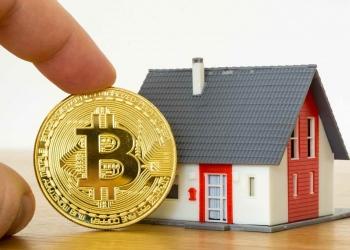 Moneda Bitcoin y un modelo de casa.