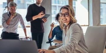 Emprendedora trabajando en una computadora portátil en la oficina. Estrategia para atraer seguidores a la tienda en línea.