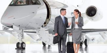 Hombre y mujer (viajeros) de negocios hablando mientras se alejan del avión.