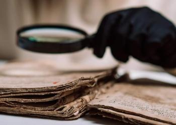 Científico historiador con guantes leyendo libro antiguo con una lupa.