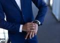 Elegante joven empresario con smartwatch de pie frente a la oficina moderna.