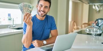 Hombre sostiene billetes de dólares americanos en casa frente una computadora portátil.