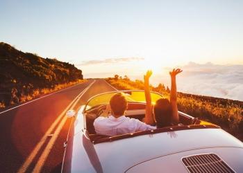 Pareja feliz conduciendo por la carretera hacia el atardecer en un coche deportivo clásico de época.