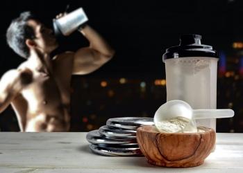 Hombre tomando batido de proteínas WHEY acompañado por pesas.