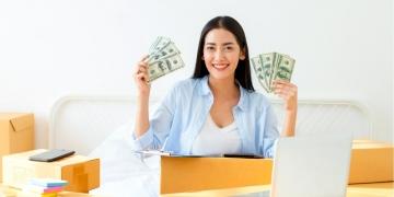 Mujer emprendedora con dólares en efectivo en la mano.