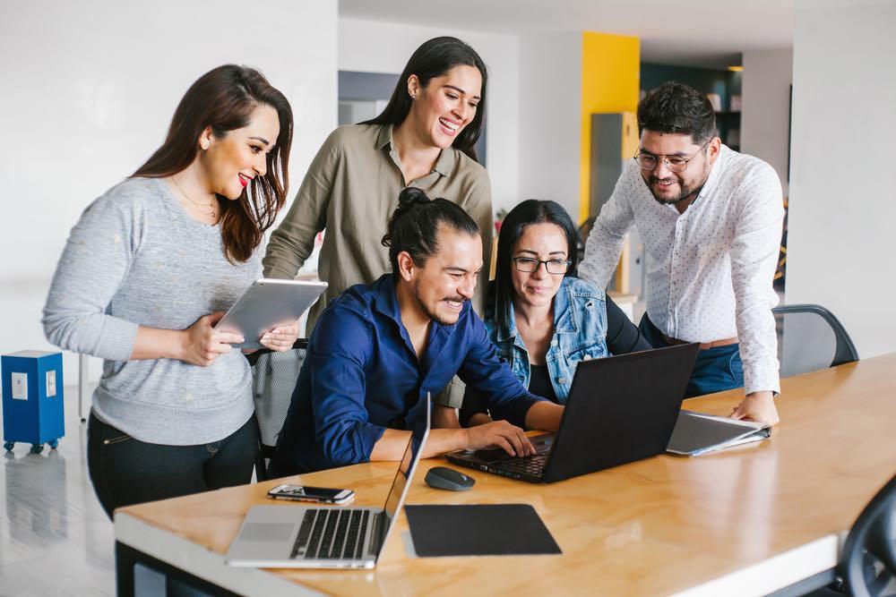 Grupo de empresarios latinos trabajando juntos en la oficina.