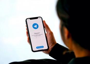 Mujer sosteniendo un iPhone 12 mirando Telegram en la pantalla.