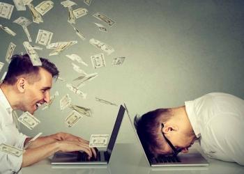 Hombre en la computadora portátil sentado junto a un hombre bajo la lluvia de dinero dólares en efectivo.