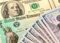 Billetes de 100 dólares con cheque de estímulo estadounidenses para coronavirus.