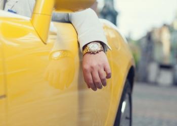 Hombre manejando coche amarillo con un reloj Rolex.