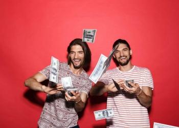 Dos jóvenes lanzando dinero en efectivo.