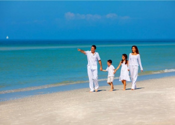 Familia feliz divirtiéndose en la arena de una playa soleada.