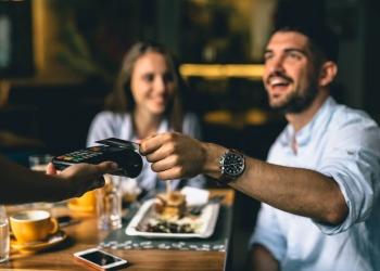 Pagando en un restaurante con tarjeta de crédito.