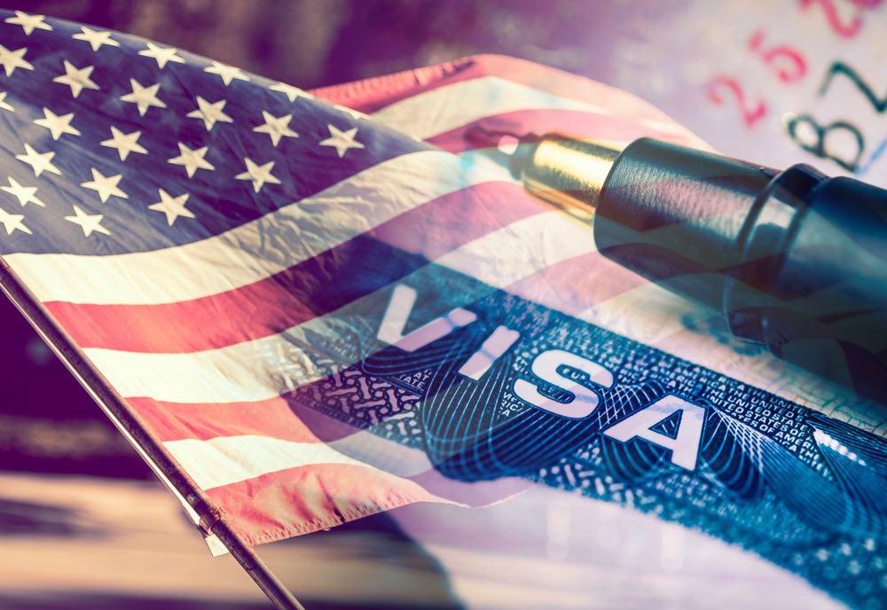 Visa de los Estados Unidos con la bandera americana en el fondo.