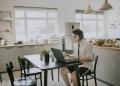 Joven asiático sentado usando una computadora portátil en su casa para una videoconferencia.