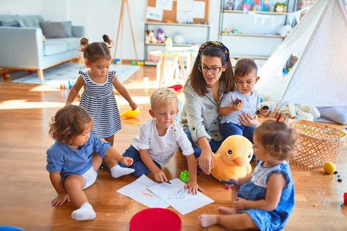 Maestra y grupo de niños pequeños dibujando con papel y lápiz en el jardín de infantes.