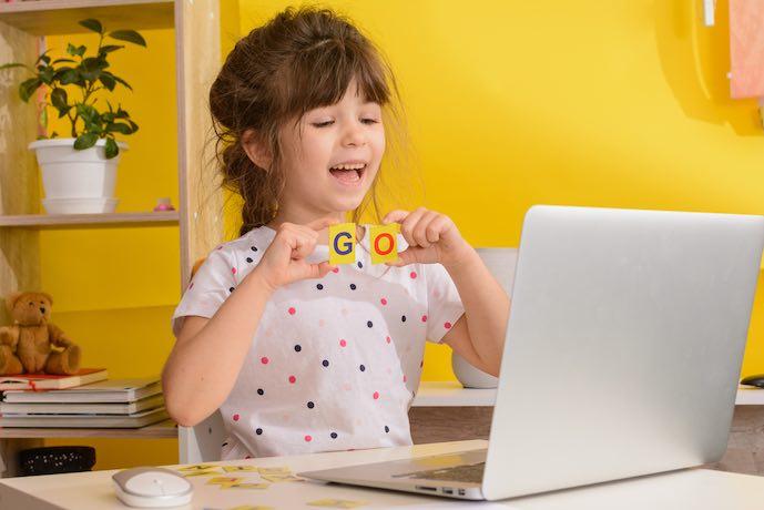 Niños aprenden inglés onlinea en casa. Educación en el hogar y educación a distancia. Niña estudia en línea. videollamadas.