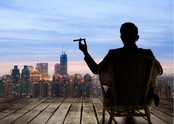 Multimillonario sentado en una silla, sostiene un cigarro y mira la ciudad en la noche.