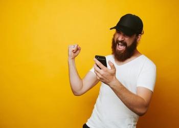Hombre barbudo celebra el éxito del juego mirando su teléfono