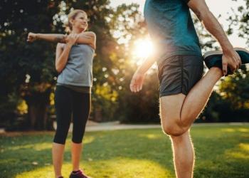 Hombre y mujer joven estirando en el parque en la mañana.
